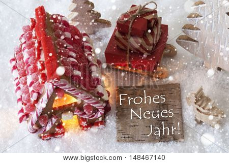 Label With German Text Frohes Neues Jahr Means Happy New Year. Gingerbread House On Snow With Christmas Decoration Like Trees And Moose. Sleigh With Christmas Gifts Or Presents And Snowflakes.