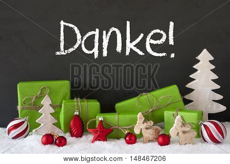 German Text Danke Means Thank You. Green Gifts Or Presents With Christmas Decoration Like Tree, Moose Or Red Christmas Tree Ball. Black Cement Wall As Background With Snow.