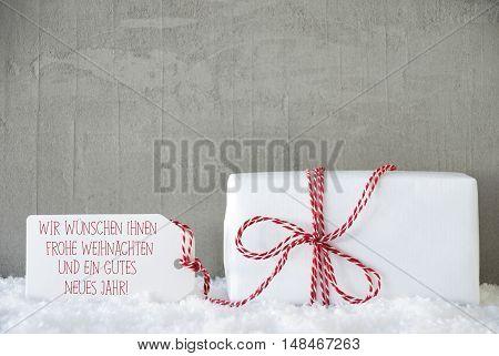 Label With German Text Wir Wuenschen Ihnen Frohe Weihnachten Und Ein Gutes Neues Jahr Means Merry Christmas And Happy New Year. One Present On Snow. Cement Or Concrete Wall As Background.