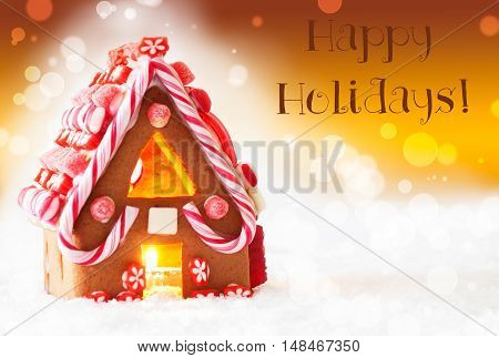 Gingerbread House In Snowy Scenery As Christmas Decoration. Candlelight For Romantic Atmosphere. Golden Background With Bokeh Effect. English Text Happy Holidays