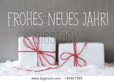 German Text Frohes Neues Jahr Means Happy New Year. Two White Christmas Gifts Or Presents On Snow. Cement Wall As Background. Modern And Urban Style.