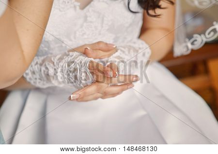 Beautiful bride's hands with manicure in white gloves.