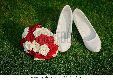 wedding bouquet and the bride's white shoes on grass.