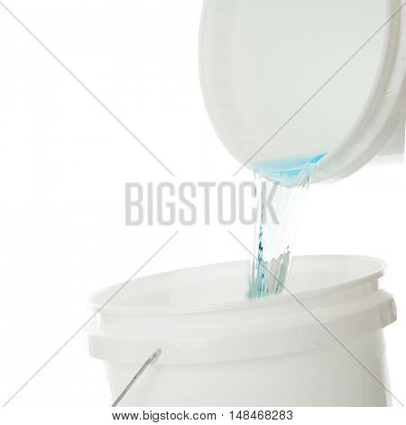 Close-up of water being poured from one bucket into another.  On a white background.