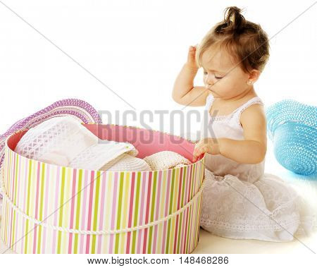 An adorable baby girl sitting in her petticoat trying to decide which to wear from a large hat box filled with girly spring hats.  On a white background.