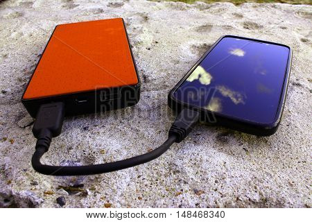 Brown powerbank and smartphone on concrete background angle view