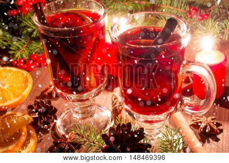 christmas mulled wine with spices and orange in the candle light with snow texture. festive romantic drinks background