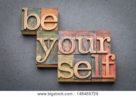 be yourself word abstract in letterpress wood type blocks against gray slate stone