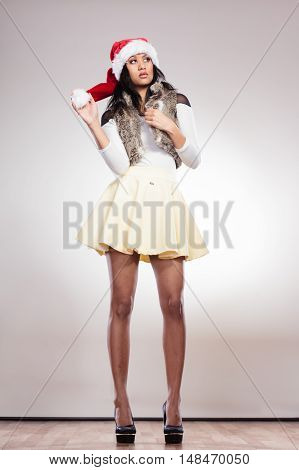 Christmas winter happiness concept. Full length of fashion woman girl mixed race wearing santa helper hat on gray