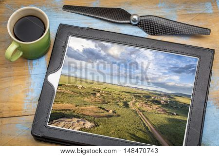 aerial photography concept - reviewing pictures of prairie landscape on a digital tablet with a cup of coffee
