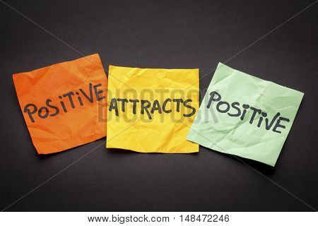 positive attracts positive - law of attraction concept - colorful sticky notes against black paper