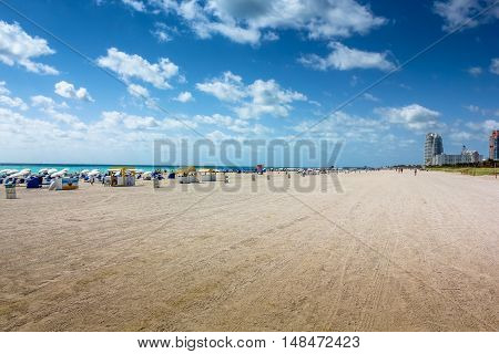 Beach umbrellas, deck chairs and people sunbathing in the South Beach neighborhood of Miami Beach in Florida. South Beach is famous for its tropical sea, the long white beaches and nightlife.