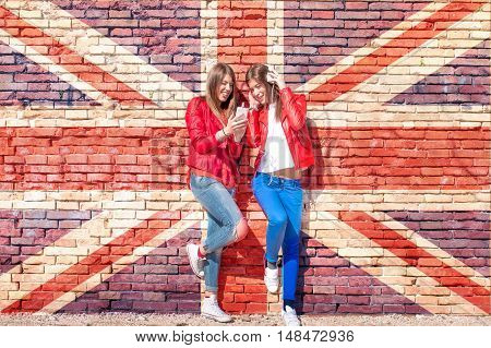 british rock scene concept - two girls listening to music on smartphone standing agaist a brick wall  background painted with british flag or union jack