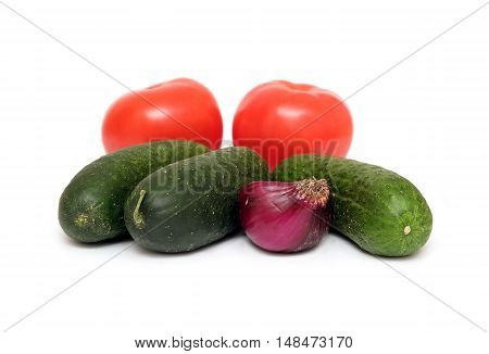 Fresh vegetables isolated on white. Cucumbers, tomatoes and onion front view closeup