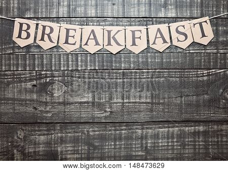 Breakfast sign with paper letter on wooden table. For text below