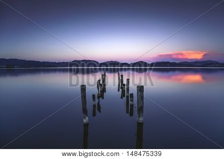 Wooden pier or jetty remains on blue lake sunset and sky reflection water. Long exposure Versilia Massaciuccoli Tuscany Italy.
