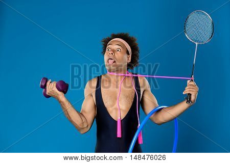 Young handsome sportive african man posing with dumbbells, hoop, skipping rope, racket over blue background. Copy space.