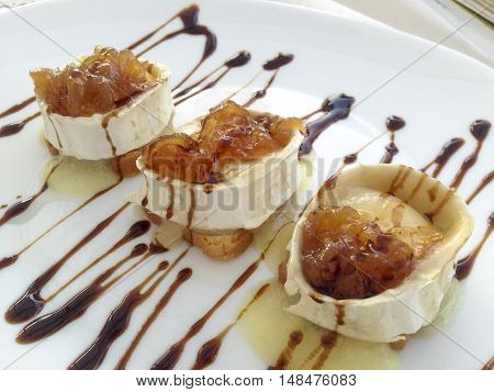 Goat cheese rolls with caramelized onions decorated with black vinegar sauce. Spanish tapa