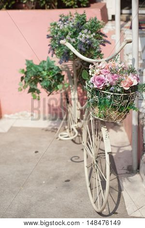Parked retro bike with basket full of flowers