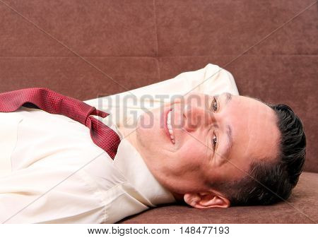 Man lying in the  living room smiling