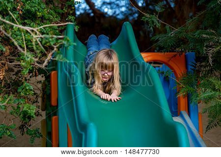 A little blond girl goes down a slide head first with her tongue hanging out in concentration.
