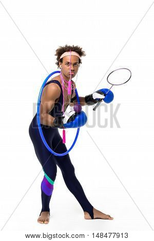Young handsome sportive african man posing with boxing gloves, hoop, skipping rope, racket over white background. Copy space.