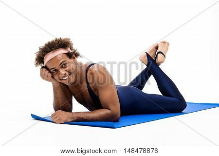 Young handsome sportive african man smiling, lying on karemat over white background. Copy space.