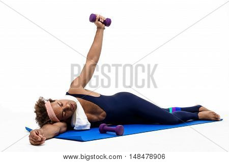 Tired young handsome sportive african man lying on karemat over white background. Copy space.
