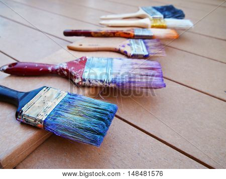A row of used stained paintbrushes in various colors drying on a deck after a house painting project.