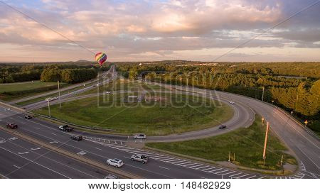 Aerial picture of hot Air Balloon flying low on the middle of a major highway in North Georgia during sunset