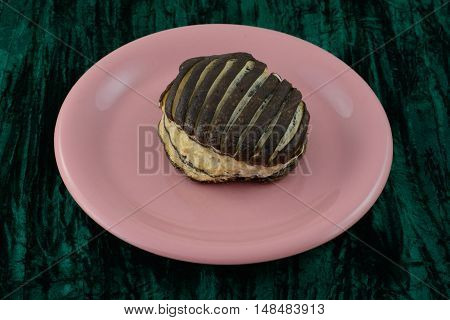 Chocolate eclair pastry with chocolate icing on pink plate