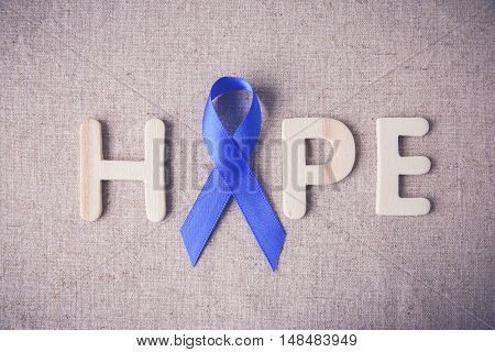 Blue ribbon with HOPE word toning background Colon Cancer Colorectal Cancer Child Abuse awareness