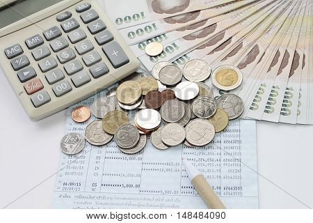 Concept of savings : Coins, Thai Baht money, calculator and pen on savings account passbook