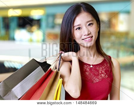 young asian woman on shopping spree carrying paper bags on shoulder walking in mall happy and smiling