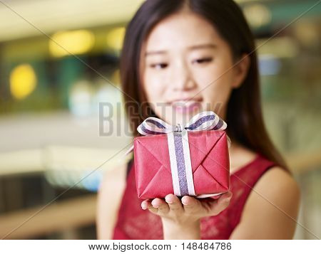 beautiful young asian woman showing a wrapped gift selective focus on the gift box