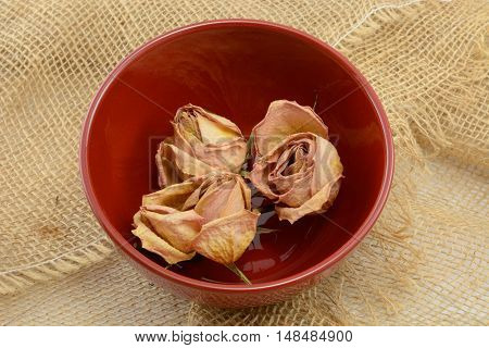 Dried peach rose blossoms in red bowl on burlap