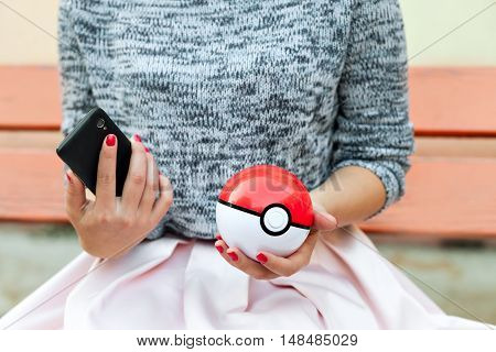 Irkutsk, Russia - September 15, 2016, an editorial image: outdoor game on smartphones in the Pokemon go application. Pokeball instance advertising in the girl's hand. Play Pokeball - this equipment to catch Pokemon in the game Pokemon go.