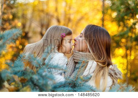 Family walk. Mother hugging and kissing daughter. Autumn Park. Cute family relationships.