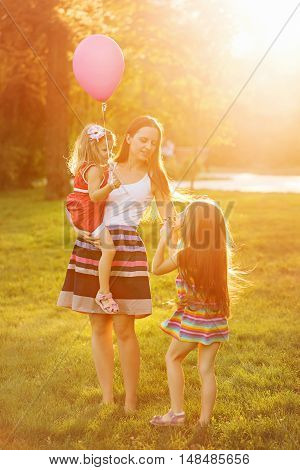 Mother and two daughters for a walk in the park. Mother holds daughter on hands. Family time together. Cheerful picnic.