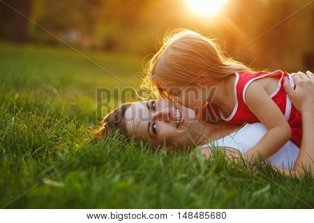 Mother and daughter lying on the lawn. Daughter kiss her mother on the cheek. Family in the city park outdoors. Happiness of motherhood and childhood.