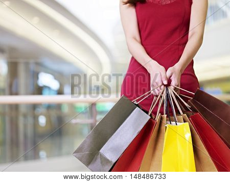 young woman female shopper standing with colorful paper bags in hands in shopping mall or department store