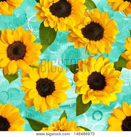 Seamless pattern made up by photos of yellow sunflowers with green leaves, on a teal blue watercolor texture with hand painted circles