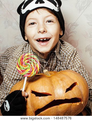little cute boy with halloween pumpkin close up holding candy, trick or treat smiling happy