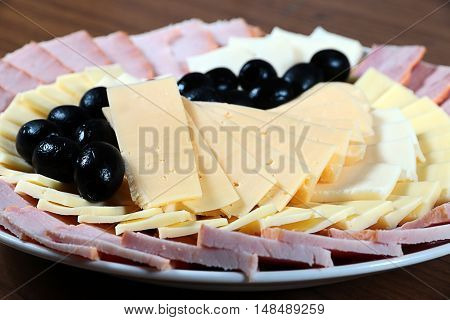 several kinds of sliced cheese and bacon on a plate