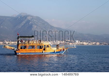 TURKEY ALANYA - NOVEMBER 10 2013: Vacationers tourists on a small cruise ship in the Mediterranean Sea near the coast of Alanya. Boating is very popular in the Mediterranean in cities such as Antalya Alanya Marmaris and other.