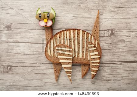 Funny cat made of bread and vegetables on wooden background