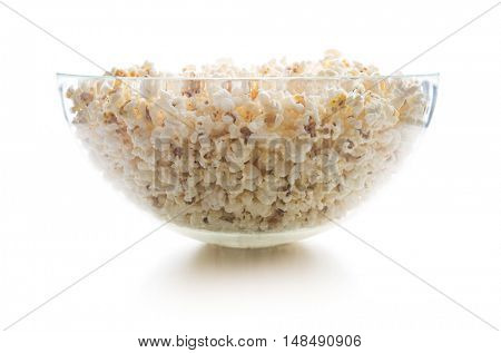 Tasty salted popcorn in big glass bowl isolated on white background.