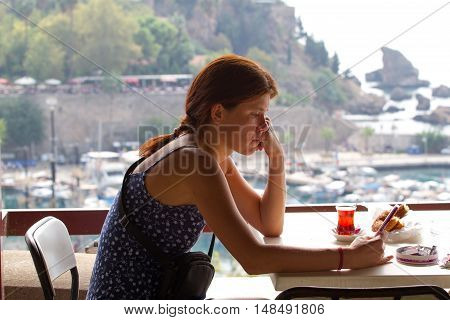 Upset girl sitting in cafe and leafing through a smart phone. Antalya, view old city, landscape