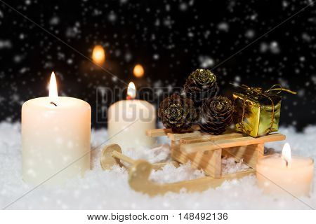 Wooden Sledge With Gifts And White Candles In The Snow, Snowing Background