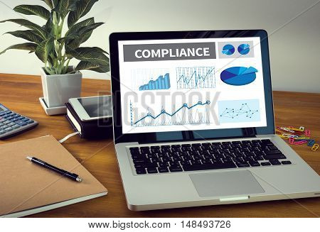 COMPLIANCE Laptop on table. Warm tone businessman working